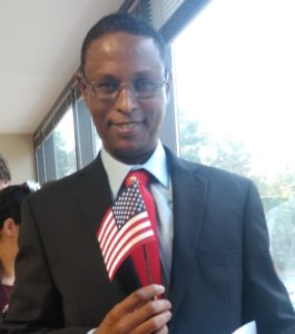 Abdirahman holding a small American Flag