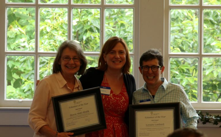 two people being presented with Volunteer of the Year award from New American Pathways
