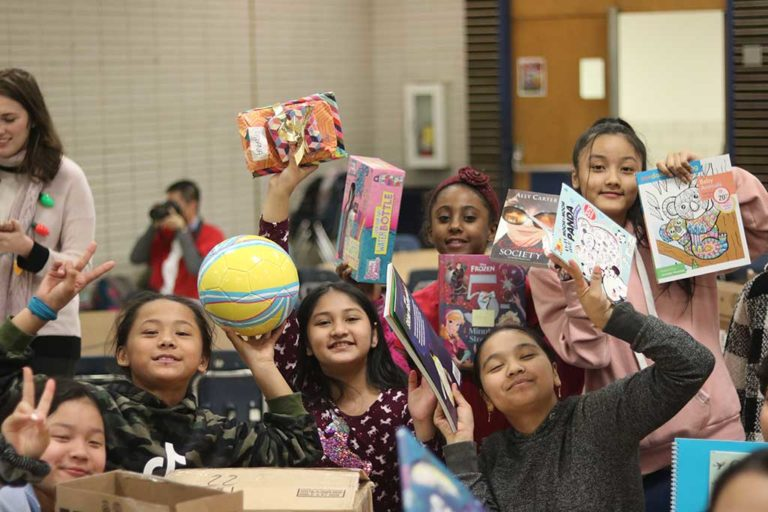 Group of children holding up donated items