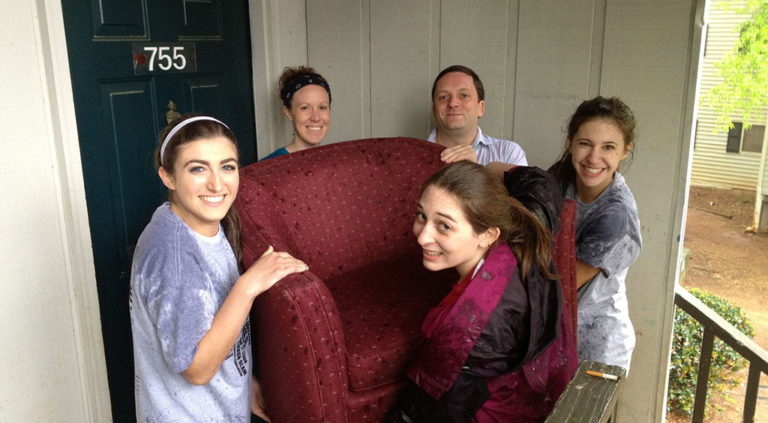 group of volunteers helping to move chair