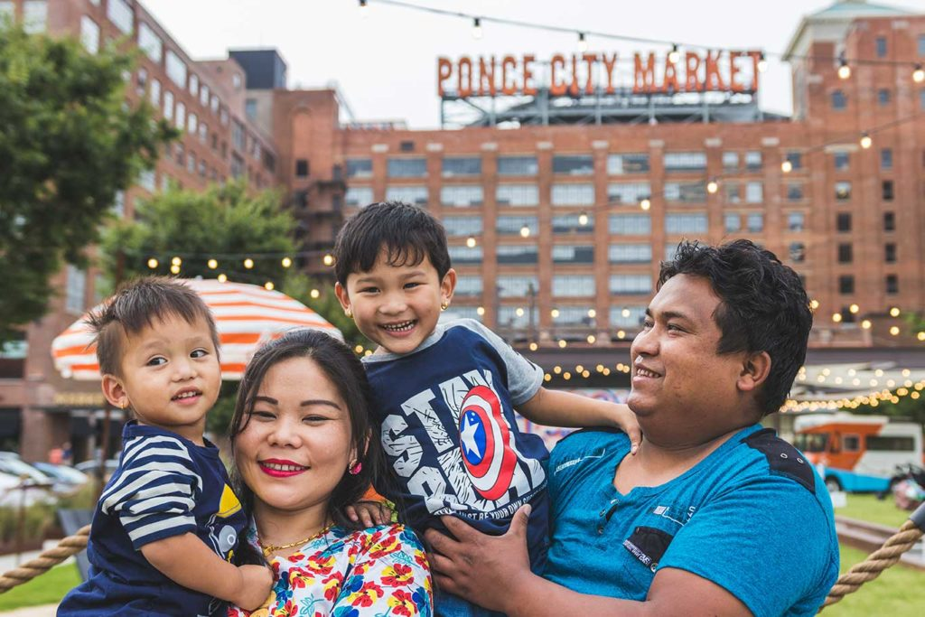 The Suk Rai family in front of Ponce City Market building