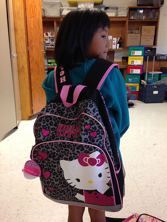 Young girl showing off her Hello Kitty backpack