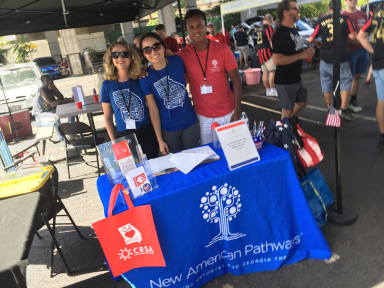 Three New American Pathway volunteers standing at a booth at an Atlanta United game