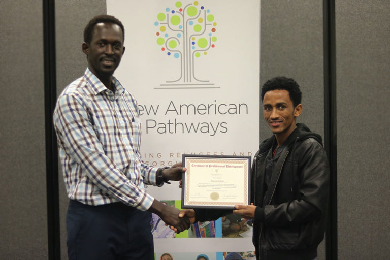 man recieving a Certificat of Professional Development award from New American Pathways